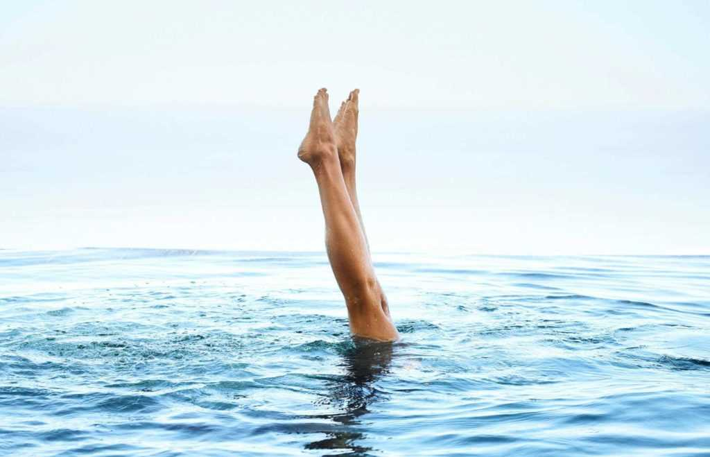 a woman's two legs standing upright out of fresh blue water