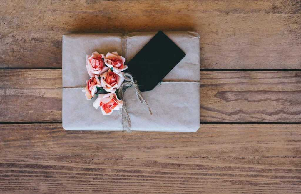 a paper wrapped gift with flowers and a card