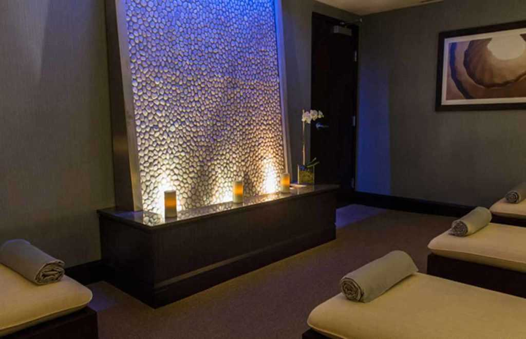 inside a massage room with a relaxing waterfall in dim room