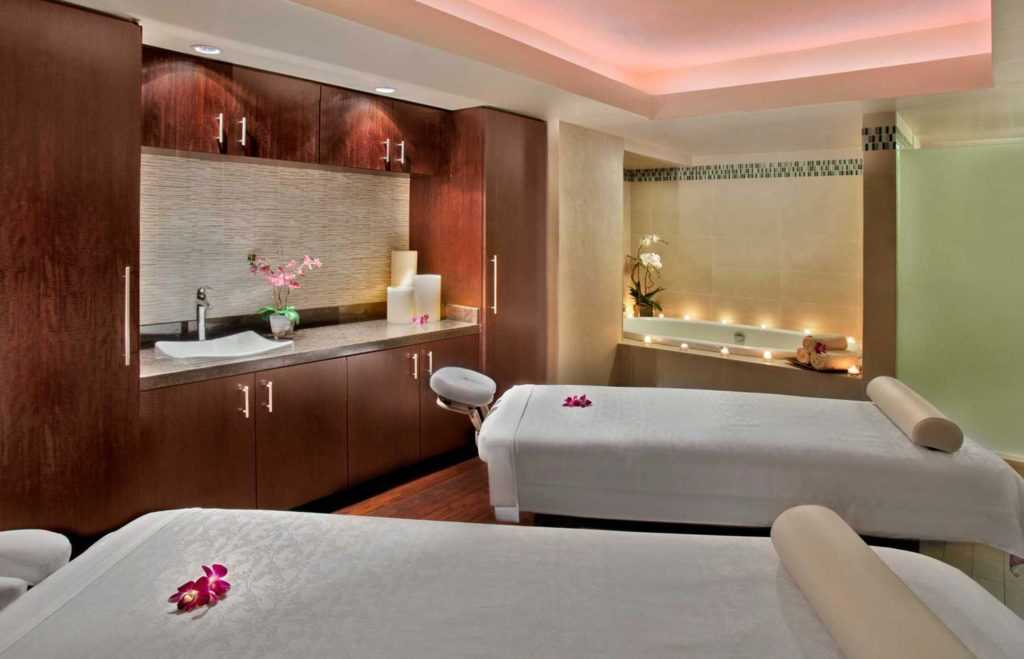 two intimate massage beds in a room with candles lit