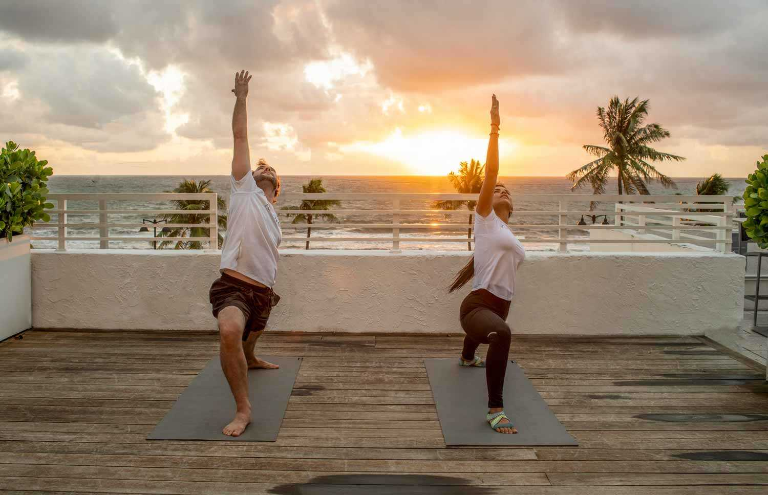 man and woman doing yoga during sunset