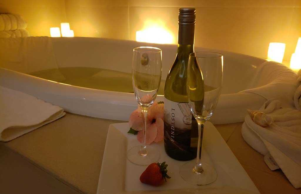a bottle of wine and two glasses sit by a full bathtub surrounded by glowing candles