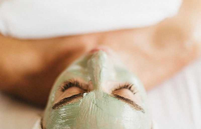 woman laying relaxing during a facial mask at a spa