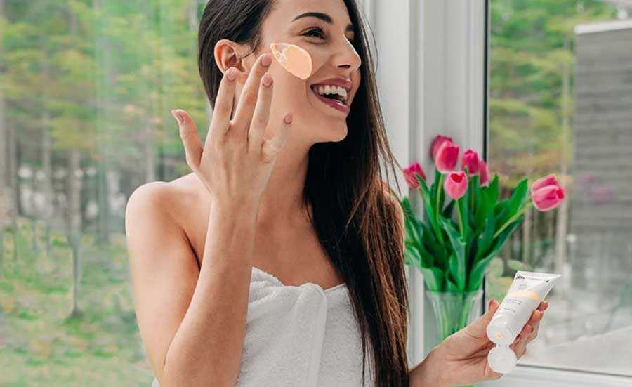 woman holding a bottle of cream and spreading some on her face with the other hand