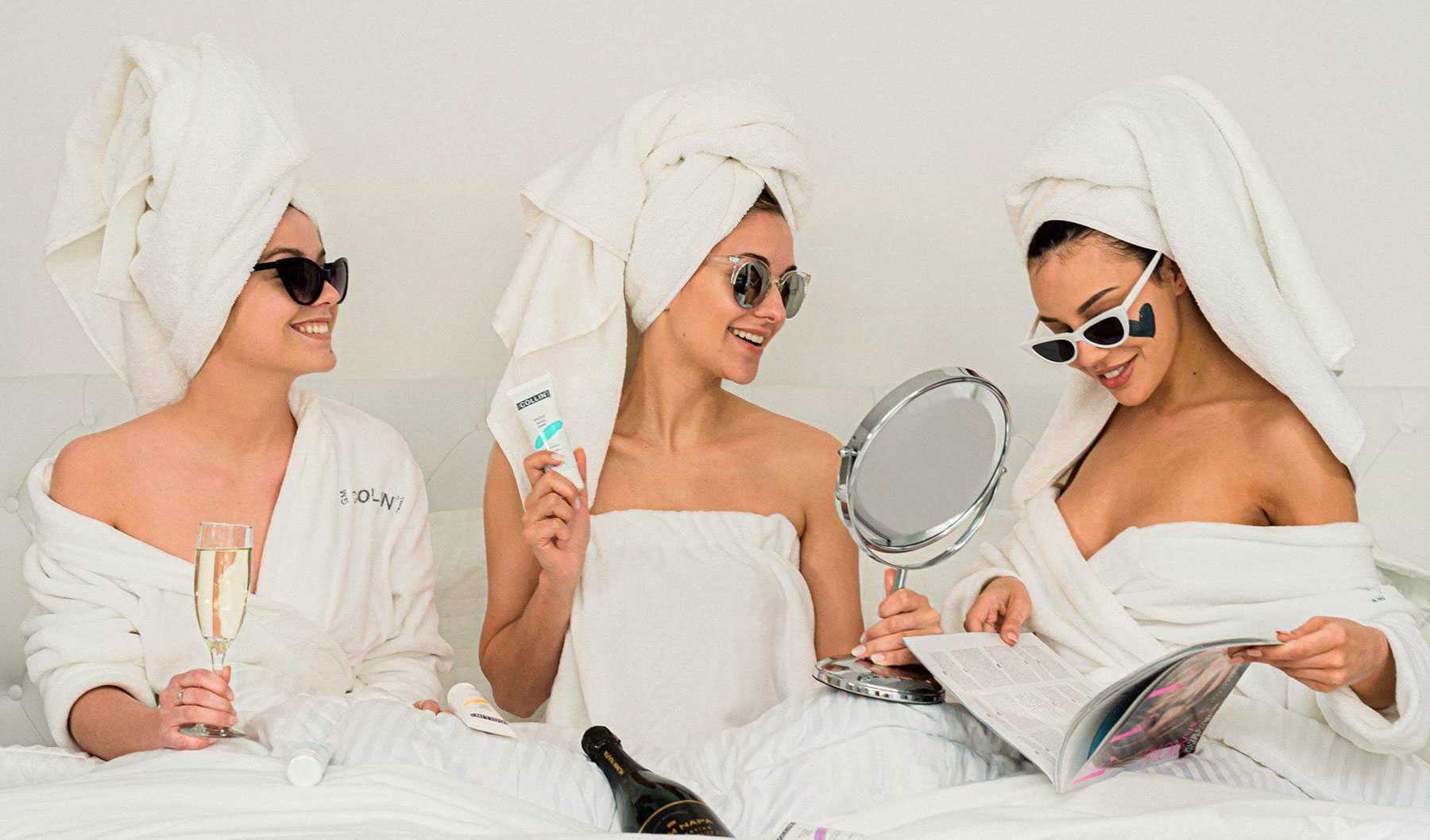 three women in white dressing gowns and white towels on head enjoying champagne